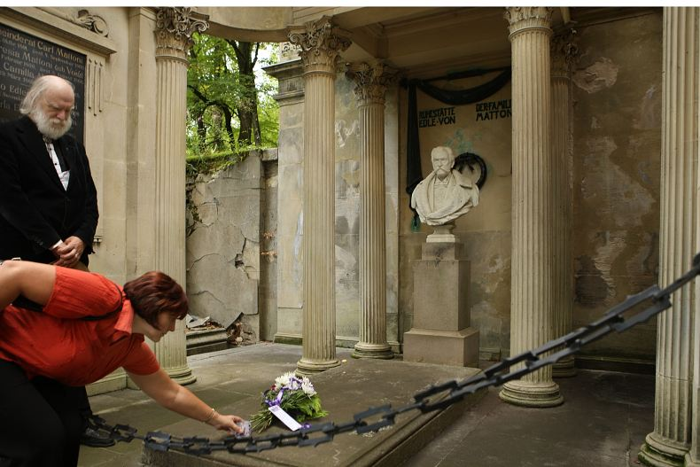 Členka prezidia ASORKD upravuje květinu položenou na hrob Heinricha von Mattoniho